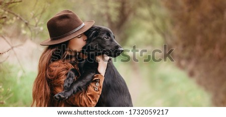 Pretty young girl holding her puppy retriever dog in the nature, sharing a hug, cuddling, kissing. Animal best friend, lovely friendship