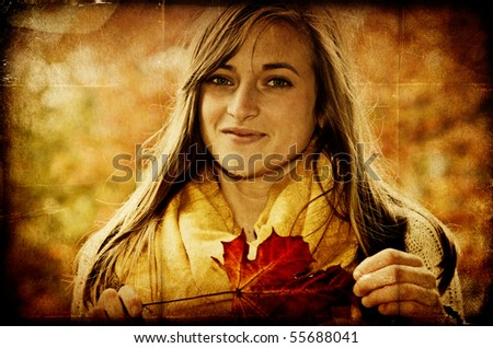 Pretty young girl holding vibrant red maple leaf