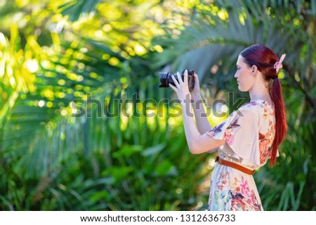 Pretty young girl in a floral summer dress out in the garden taking photos with her camera