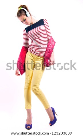 Pretty young girl isolated on white wearing bright casual clothes like yellow pants, stripped red white and blue shirt, pink vest,  purple high heels, listening to music via headphones and dancing.