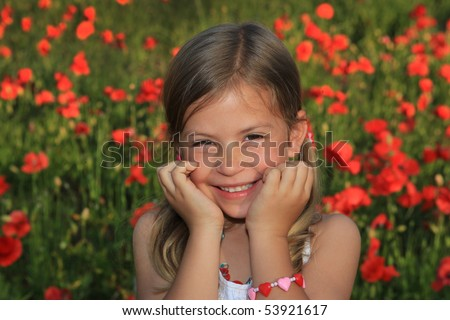 Pretty young girl laughing in a poppy field