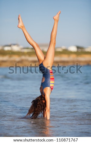 pretty young girl makes a handstand in the sea