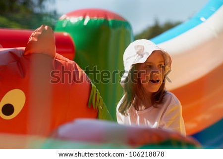 Pretty young girl posing in a bouncing castle in a bright sunny day with beautiful smile