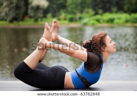 Pretty young girl practicing yoga near the lake