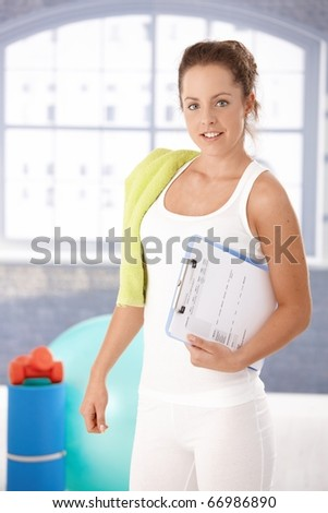 Pretty young girl prepared for personal training in gym, holding her training plan in hand.?