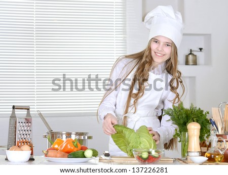 Pretty young girl preparing food in the kitchen