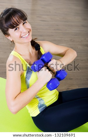 Pretty young girl pump stomach with dumbbells exercises
