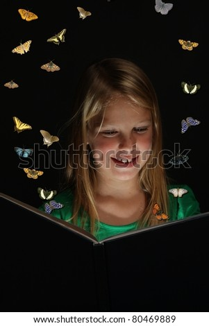 Pretty young girl reading a fairytale book with butterflies emerging