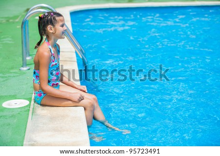 Pretty young girl sit at pool's edge