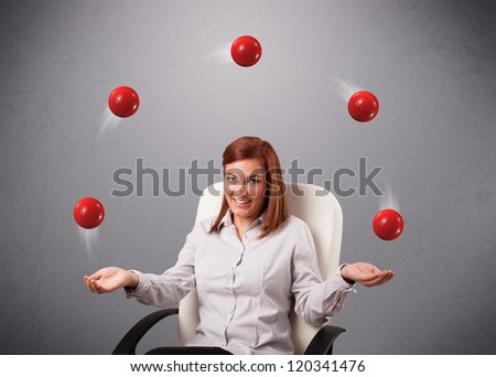 pretty young girl sitting and juggling with red balls