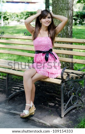 Pretty young girl sitting on a park bench