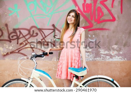 Pretty young girl smiling with long blond-brown hair, in pink head wrap and dress with a pattern of flowers. Holding vintage bicycle on urban graffiti background.