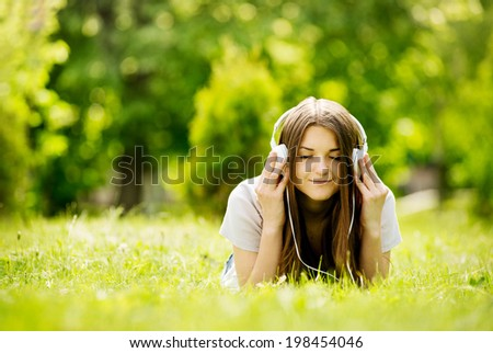 Pretty young girl smiling with pleasure as she listens to music with her eyes closed in bliss while lying on her stomach on the grass in a green lush garden enjoying the spring sunshine