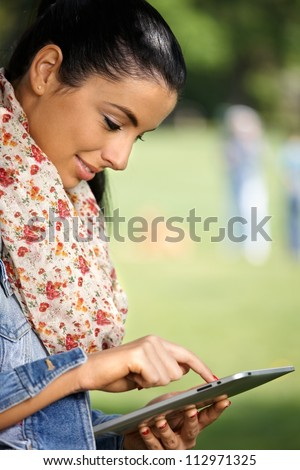 Pretty young girl using tablet PC in park, smiling, side view.