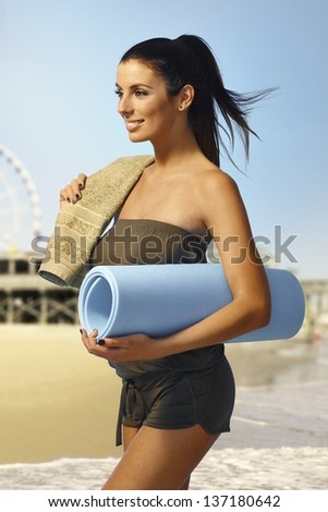 Pretty young girl walking on the beach with beach mattress and towel, smiling happy.