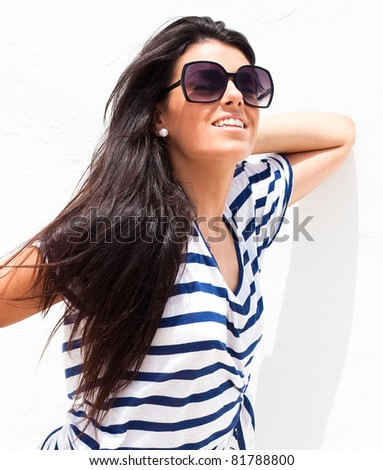 pretty young girl wearing a striped t-shirt and sunglasses, outdoor shot