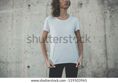 Pretty young girl wearing blank white t-shirt with area for your logo or design, mock-up of template white t-shirt, concrete wall in the background