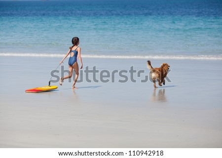pretty young girl with a surfboard and her cute Elo puppy running at the beach to the water