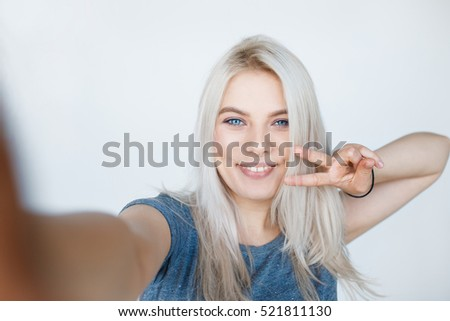 Pretty young girl with blond dyed hair smiling and taking selfie while showing two fingers peace sign