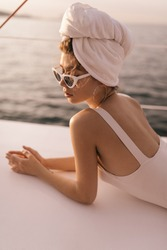 Pretty young girl with light swimsuit, towel on head and stylish sunglasses resting and looking down against background of sunlit sea in summer