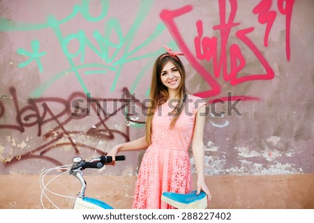 Pretty young girl with long blond-brown hair, in pink head wrap and dress with a pattern of flowers. Holding vintage bicycle on urban graffiti background.