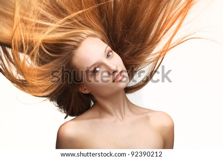 Pretty young girl with long flying hair on white background