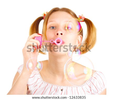 Pretty young girl with soap bubbles over white
