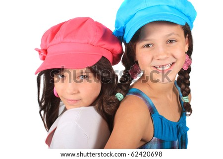 Pretty young girls in the ages of eight and ten who could be sisters or best friends dressed in colorful clothing and hats