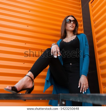 Pretty young hipster woman in stylish clothes in trendy sunglasses in trendy sandals poses near the modern orange metal wall in the city on a summer day. Attractive urban girl fashion model outdoors. #1423250648
