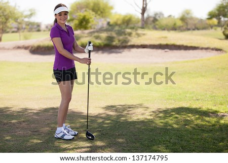 Pretty young Hispanic woman ready to play some golf