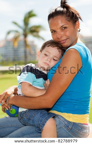 Pretty young hispanic woman with a cute young boy in an affectionate embrace outdoors in a park setting.