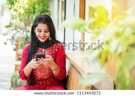 Pretty young indian woman using her phone  stock photo