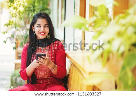 Pretty young indian woman using her phone and looking at camera stock photo