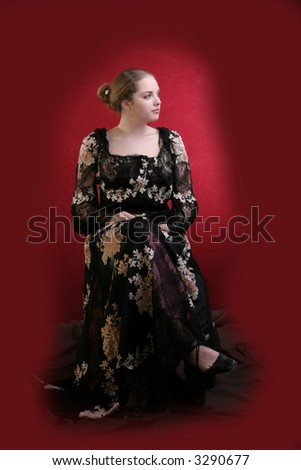 pretty young lady  in old time ball dress with black fan Standing girl with a red fan dress in  style of the beginning of XX century