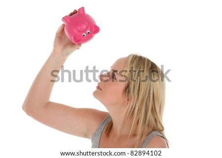 Pretty young lady looking into her pink piggy bank for money