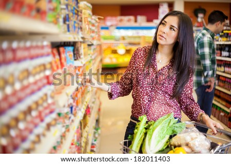 Pretty young Latin brunette picking up some food at the grocery store
