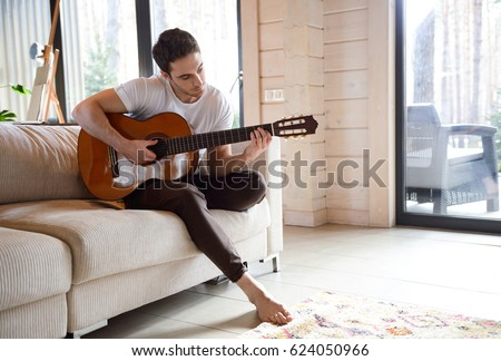 Pretty young man playing guitar while sitting on sofa in light living room
