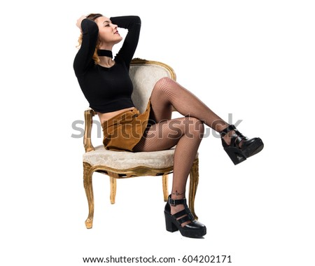 Pretty young model woman sitting on vintage armchair