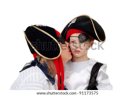 pretty young mother kissing her cute little kid, both in the pirate costumes
