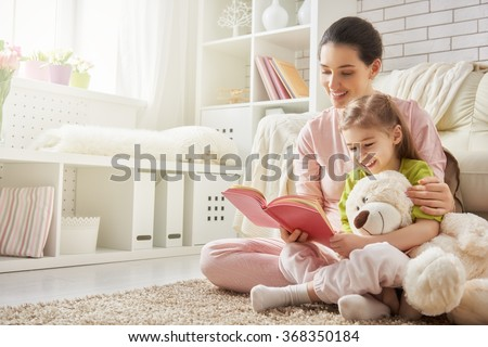 pretty young mother reading a book to her daughter #368350184