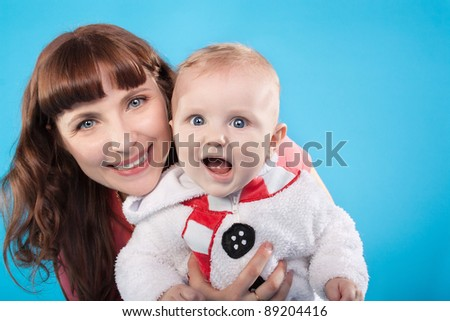 pretty young mother with the cute little baby on the blue background