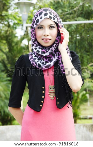 Pretty young Muslim girl held a hand phone with modern dressing style.