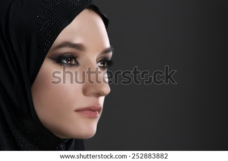 pretty young muslim woman head shot over gray background studio shot