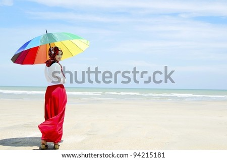 Pretty young Muslim woman looking back at beach.