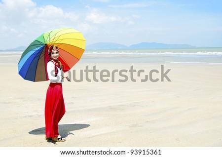 Pretty young Muslim woman walking at beach.