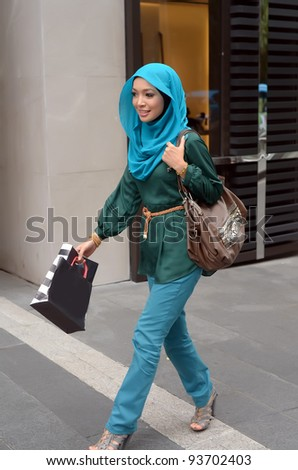 Pretty young muslim woman with holding shopping bags