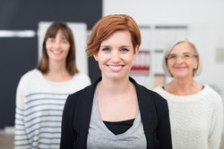 Pretty Young Office Woman Smiling at the Camera Against her Two Female Colleagues