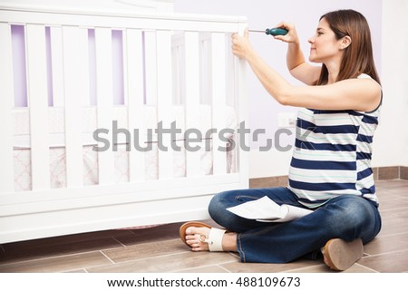 Pretty young pregnant woman assembling a baby crib in a nursery before the baby arrives
