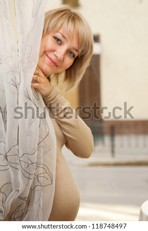 Pretty young pregnant woman looking out from the curtain