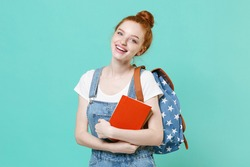 Pretty young readhead student girl in casual denim clothes with backpack posing isolated on blue turquoise background studio portrait. Education in high school university college concept. Hold books